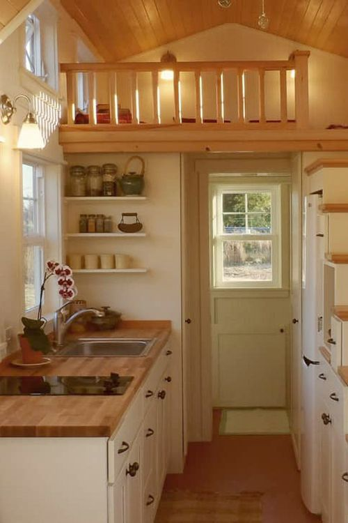 In the kitchen is an eight-foot butcher block counter with an electric cooktop, a full height refrigerator/freezer, and an oven.