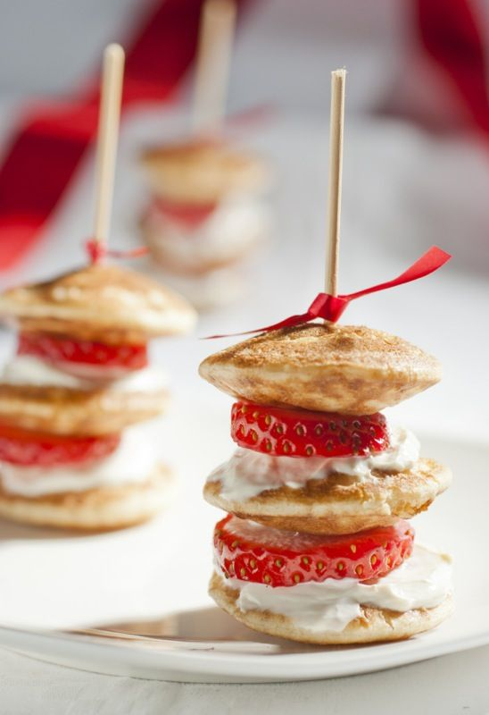 These are perfect for a brunch! Mini pancake appetizers with strawberries and whipped cream.