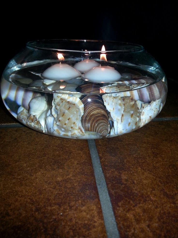 een glazen schaal met schelpen, water en drijfkaarsen. Leuk voor in de zomer, buiten... of in de winter binnen ;-)