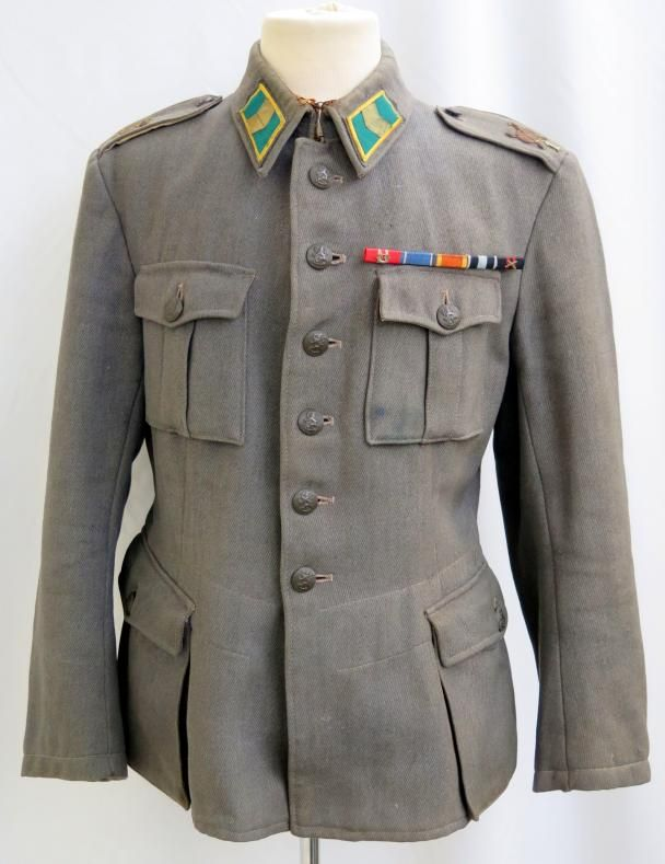 """Grey gabardine cloth made jacket. Jäger batallion 1 first-sergeant (vääpeli) tunic. Collartabs are early made with cloth backing. Green-yellow tabs fro jäger troops with first-sergeant rank. Shoulderboards with Jäger batallion 1 emblems, both patinated and other rusty. Tunic marked size 54A, maker """"Kauranen oy"""", Int and SA-marked."""