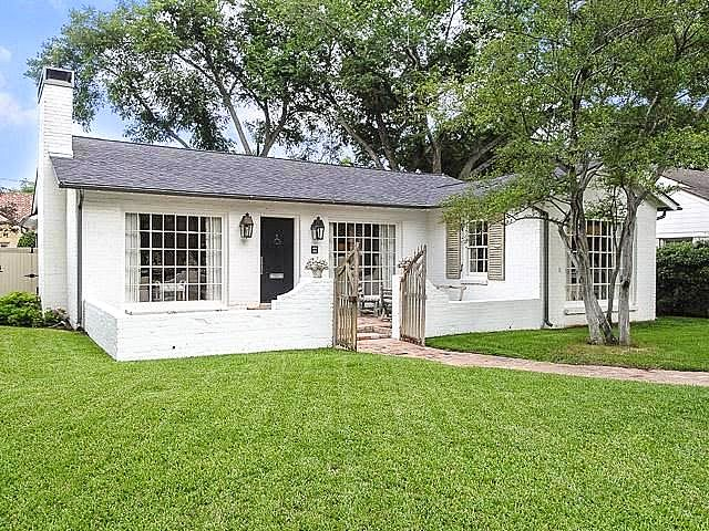 Add cottage appeal to red brick ranch by painting white, adding front patio/gates, and updating windows.