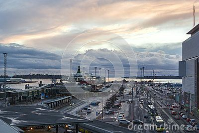 Beautiful sunset skyline and seaport with a parking area, a loading area and a passenger port with liners, cargo ships and loading cranes, a top view.