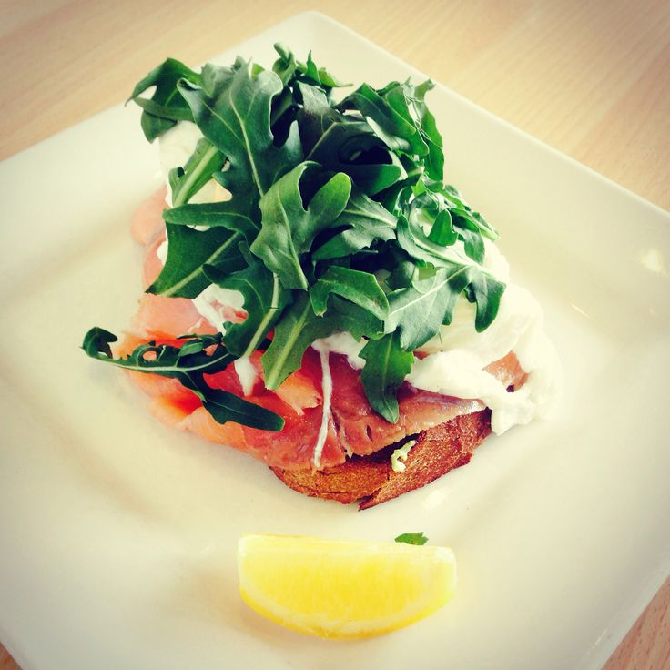 Sourdough toast with smashed avocado, smoked salmon and poached eggs topped with wild rocket.