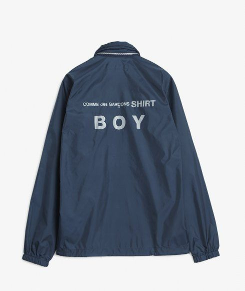 As part of Comme des Garçons SHIRT BOY collection, a coach jacket crafted from a weather resistant nylon shell. Features broad welt side pockets, stow-away hood, press stud closure, drawstring hem, cinced cuffs, and logo emblazoned across the back.