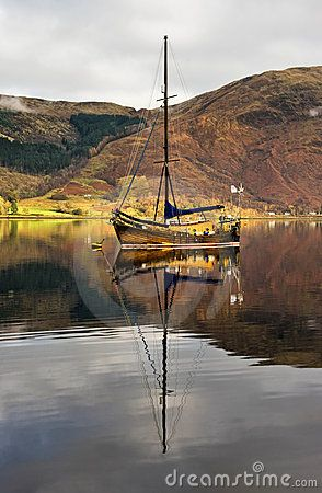 A lovely old-fashioned wooden sailing boat with tall mast reflects beautifully in the still water of Loch Leven, a sea loch, near Glencoe in the Scottish Highlands
