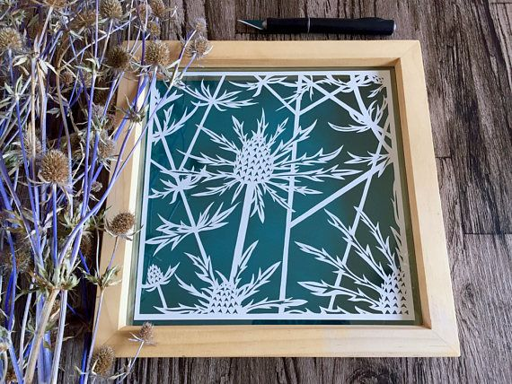 Paper art sea holly flowers in a floating frame. Floral decor that creates lovely shadows against a teal background within the frame.