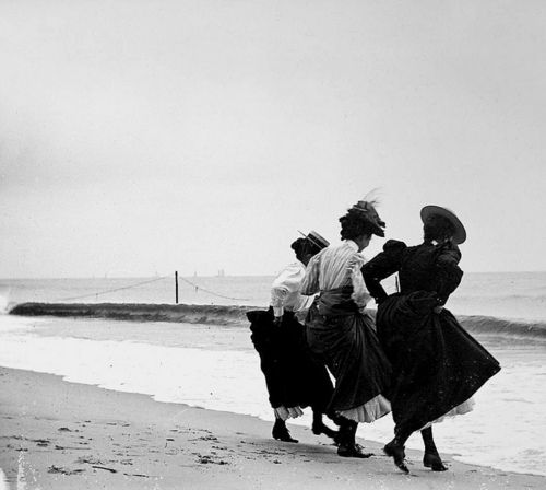 Gertrude Hubbell, Ruth Peters and Mildred Grimwood, hiking their skirts at the shoreline of the beach in Averne, Queens, New York, NY    photo by Wallace G. Levison, September 8, 1897