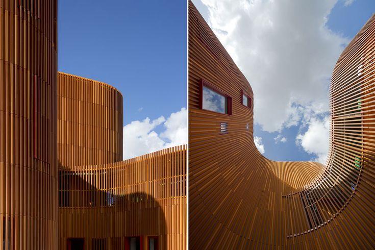 La facciata è composta da lamelle verticali in laterizio, che creano una striscia continua di volume in volume che circonda il giardino e il parco giochi. Oltre a essere l'involucro dell'edificio, il rivestimento funziona quindi anche come una recinzione per il parco giochi, come protezione delle coperture e come schermatura solare davanti alle finestre - Asilo a Copenhagen