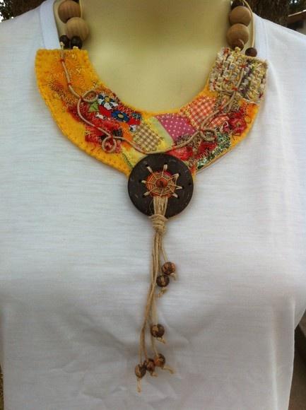Colar trabalhado sobre feltro amarelo, com aplicação de retalhos, fios, peça de côco e contas de madeira. R$50,00
