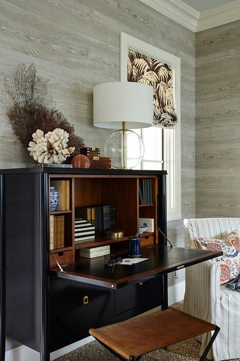 A brown leather stool is paired with a black secretary desk adorned with square brass drop pulls topped with sea coral, sea fan and an Aerin Morton Table Lamp lining a wall clad in gray faux bois wallpaper.