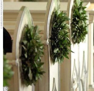 """The couple used greens to decorate the church, accented by white flowers. """"We wanted to let the chapel shine,"""" said Megan. Small bay leaf and herb wreathes decorated each pew."""