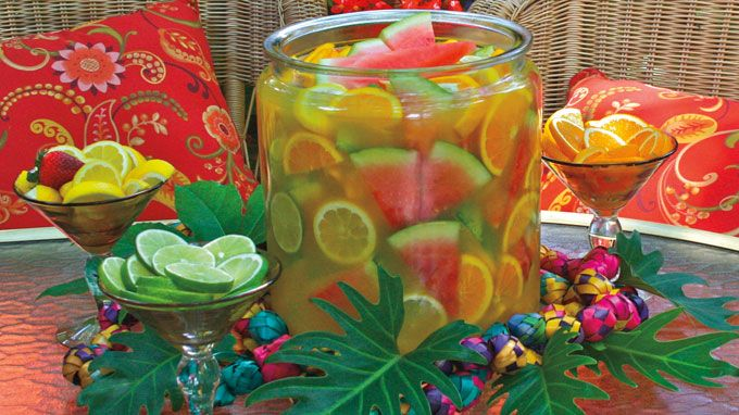 Throughout Jalisco, this refreshing drink is served in large, wide-mouthed clay bowls, called cazuelas. Citrus wedges are eaten or squeezed into the drink. Partakers pop chunks of watermelon and fresh pineapple into their mouths and sip the tequila-laced libation through a straw. Cazuelas inspired this party punch. Present it in an agua fresca jar to …