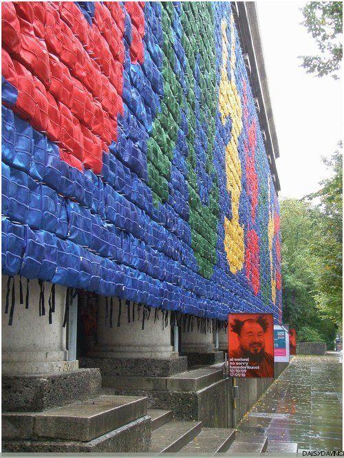 """Remembering, 2009, 9000 sacs à dos (de couleur) d'écoliers placés sur la façade de la Haus der Kunst à Munich, avec la citation d'une des mères endeuillées, """"Elle a vécu heureuse en ce monde pendant sept ans""""."""