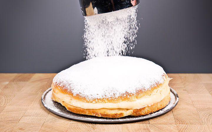 Ekmek hamurunu andıran mayalı bir hamur arasında bol krema, üzeri bol pudra şekeri. Yanında da dumanı üzerinde bir fincan kahve.