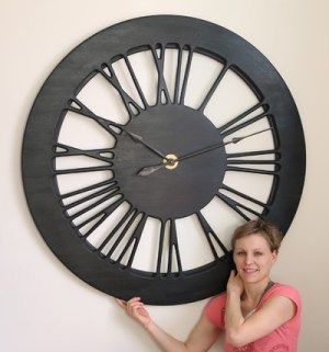 """The """"Light Heban XL"""" is an Extra Large Skeleton Wall Clock that is handmade from a single massive panel of sustainably sourced pine wood. It is a member of the new family of hollow giant clocks. The clock face is displaying carefully crafted Roman numerals and the wall colour is in the background. With a total diameter of 120 cm, dark frame and its classic design, the """"Light Heban XL"""" will be a statement piece of art in all interiors"""