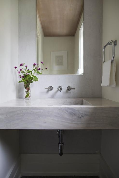 A Marble Floating Sink Vanity Is Mounted Beneath Curved Polished Nickel Towel Ring And Faucet Fixed To Slab Backsplash