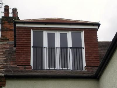 """The rear dormer is fitted with French windows and side glazing, protected by a """"Juliette"""" balcony safety rail."""