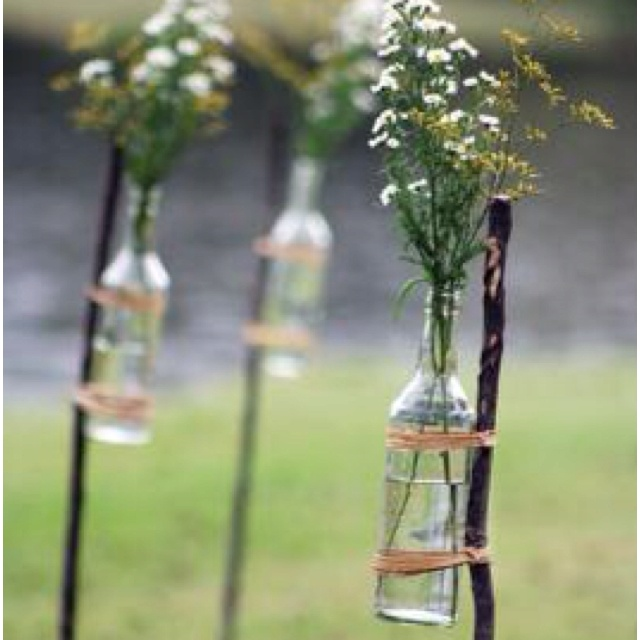 Wine bottles with flowers in tied to sticks