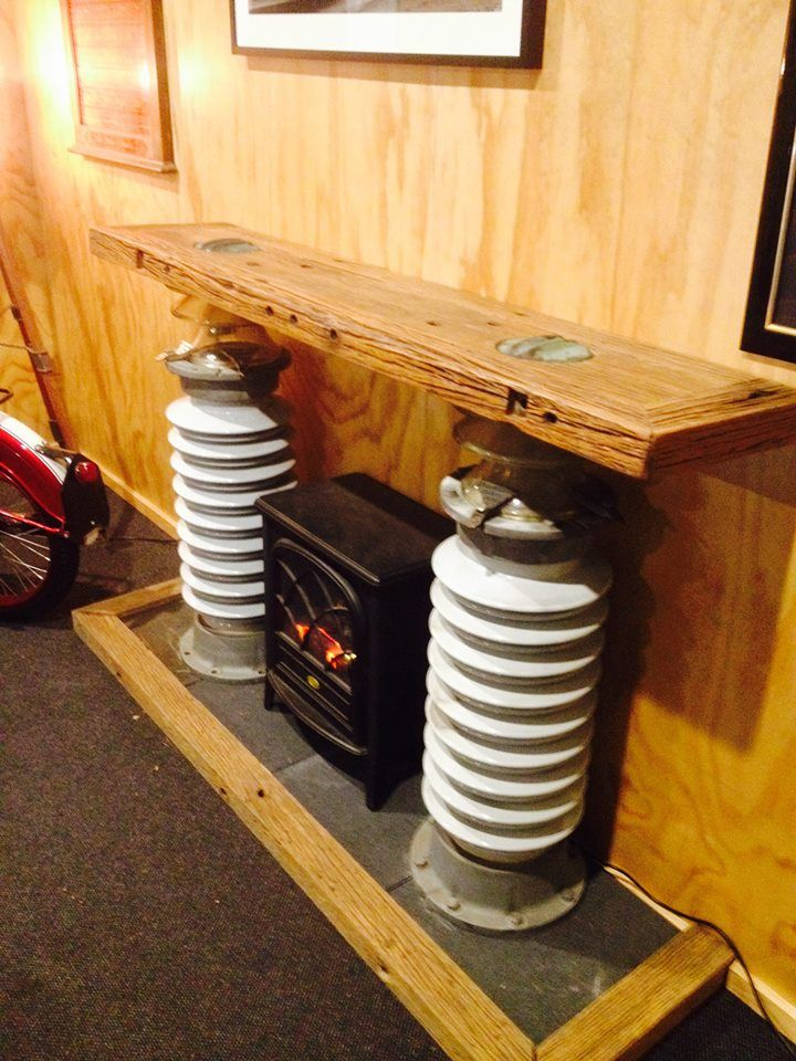 fire place mantelpiece made from large power line insulators and power poe cross arms