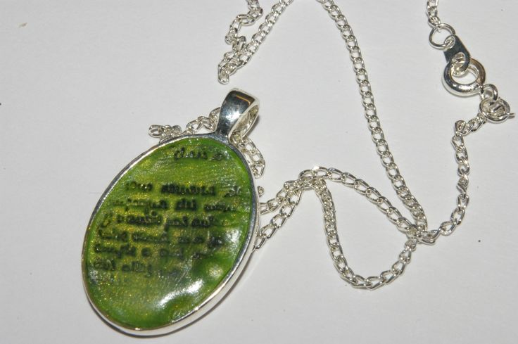handmade polymer clay pendant with printed text stamped with transparent clay on top. set in silver coloured pendant base.