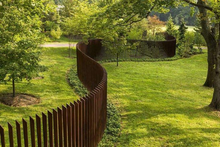 clôture de jardin moderne en lattes de bois distribuées de façon verticale