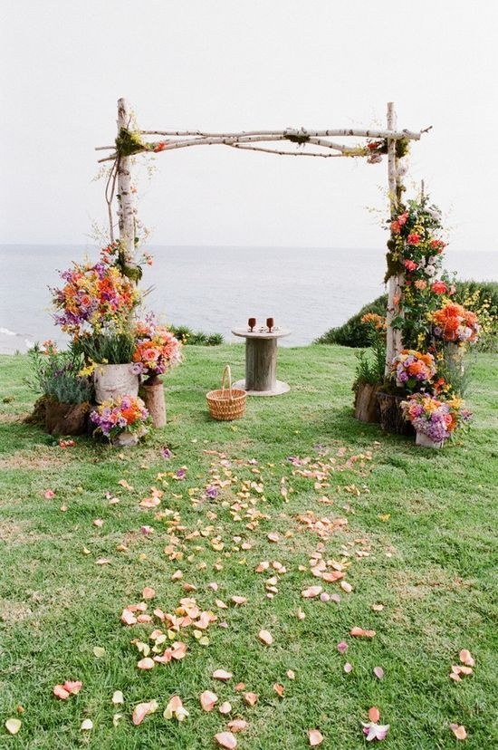 I like the idea of using the natural resources (vines, olive branches etc) to create some kind of arch/backdrop. Just don't want to detract from that gorgeous sea view. Also think that gossamer/chiffon curtains might not work as quite exposed/potentially windy?