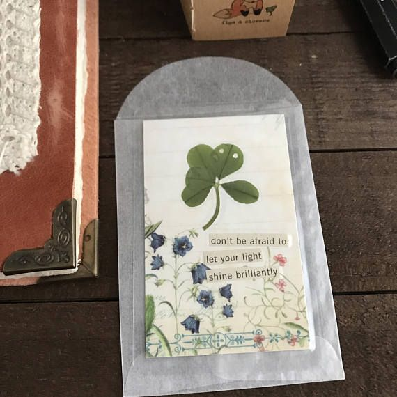 dont be afraid to let your light shine brilliantly Nature collage affirmation wallet card. This wallet card is handcrafted featuring a genuine five leaf clover. The five leaf clover was handpicked and pressed for at least two months, then sealed in a high quality, sturdy laminate