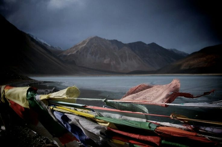 Prayer flags blow in the wind around Pangong Lake that shares itself with India and China - In Kredible Kashmir trip (14 days, 13 nights) - check us out online.