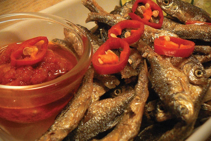 A plate full of small fried fish decorated with bright red spicy chili sauce: a truly intriguing image