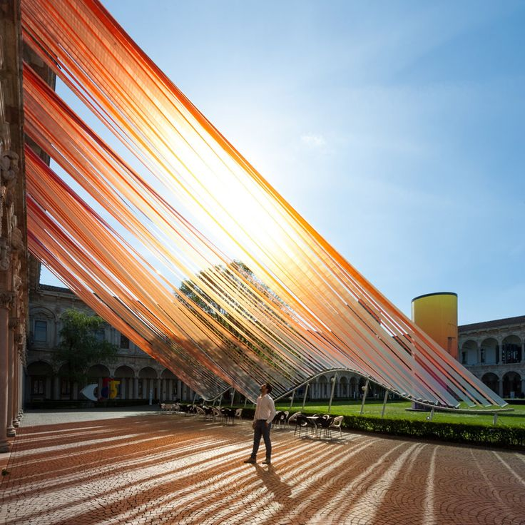 """""""Invisible Border"""" is an installation by MAD Architects in Milan, Italy. - photo by Moreno Maggi, via dezeen;  At the Cortile d'Onore courtyard at the Università degli Studi di Milano, """"lengths of ETFE plastic [are] stretched from the 15th century building down to the grassy square below. ... A wavy metal frame is used to hold the strips taught, forming an extension of the building's covered passages for visitors to walk under."""""""