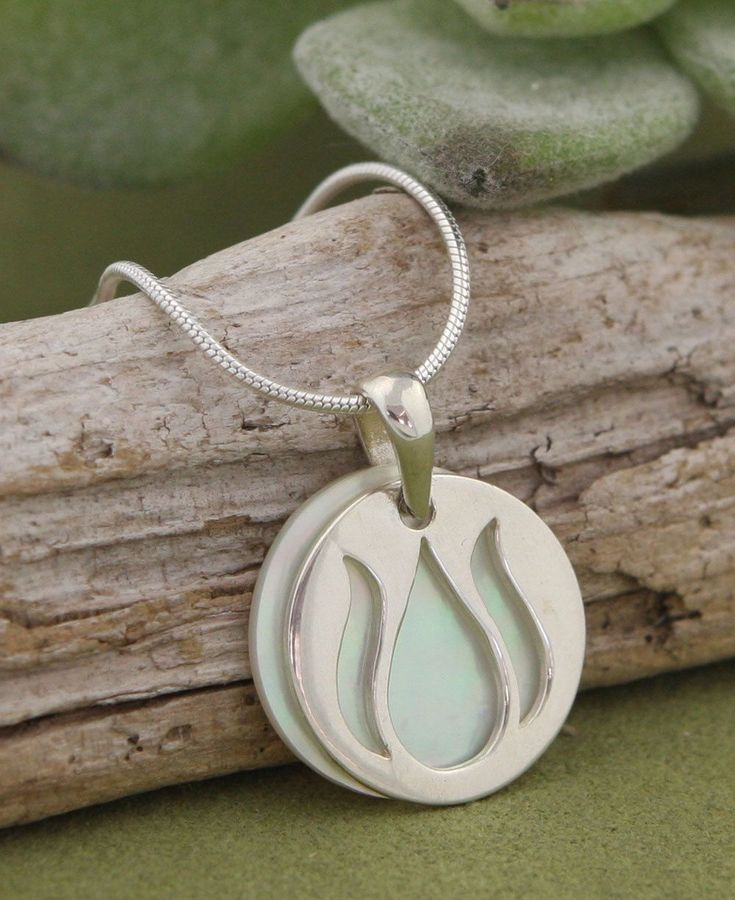 Stacked pendant features a sterling silver lotus bud cut out paired with a shimmering Mother of Pearl coin.
