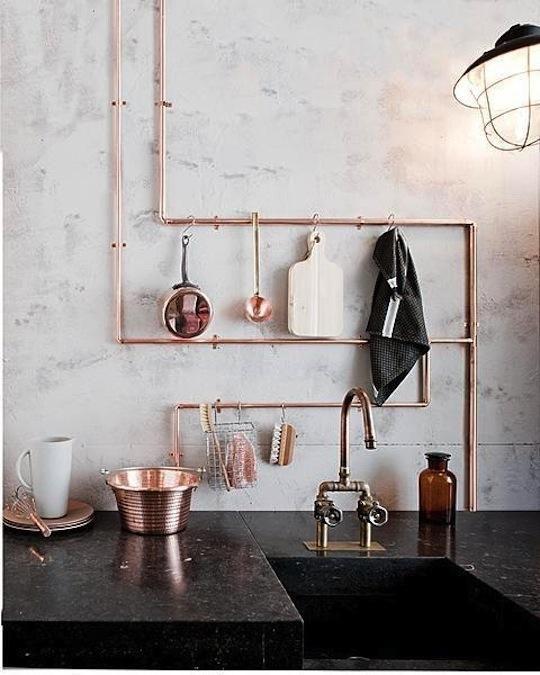 Détails de robinetterie en cuivre dans la cuisine au plan de travail noir