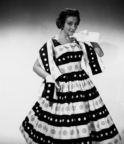 Model is wearing a square necked summer dress with broad horizontal stripes and matching stole worn with short white gloves (February 1957)