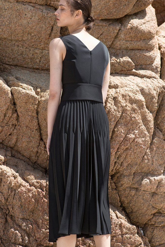 The Simma Dress in Black, featuring v-neckline, sleeveless, removable wide belt, pleated skirt. Concealed zip fastening at the back.