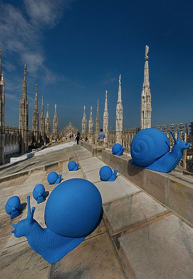 Fifty blue plastic snails slowly climbed upon Milan's duomo roof earlier this month invading the city landmark,   the gothic cathedral that took nearly six centuries to complete, in the striking artistic intervention called   'Re-generation' by Cracking Art Group.