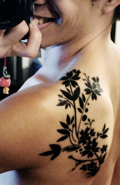 See more Black ink flower plant tattoo on back