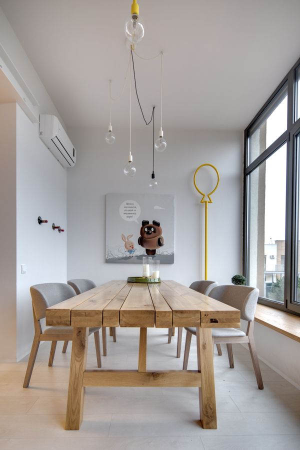 Wooden dining table and a funky art piece | Lipinka apartment in Kiev