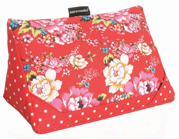 Our gorgeous Japanese Floral print stand for tablets and iPads Red floral and polka dot print Fits all tablets and ipads Brilliant for handsfree support of your gadget while watching your favourite films, youtube clips, reading, typing, great for Skype calls and Facetime. Use on the couch, in bed, in the gym, on holiday, in the car, on the train, in the kitchen, even in the office. Place tablet either in the lip at the front or in the two corner slots, your whole screen is visible. Also a...