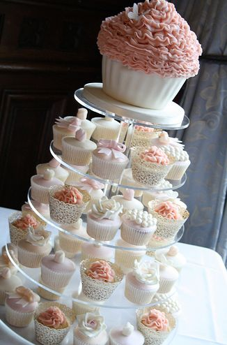 I like the idea of cupcakes instead of a cake for a wedding and the huge cupcake on top is super cute!