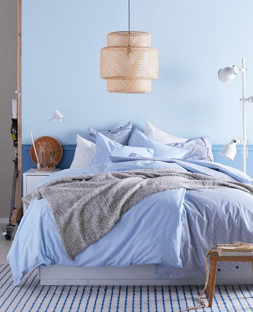 Soveværelse indrettet i hvide og lyseblå nuancer med masser af plaider og puder.