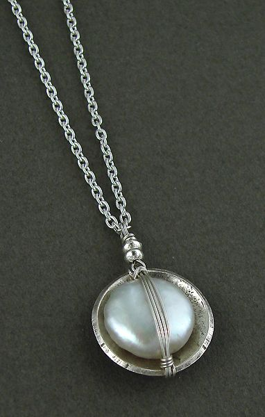 Handwrapped white freshwater pearl set in an oxidized sterling cup pendant.  16-18 adjustable chain.