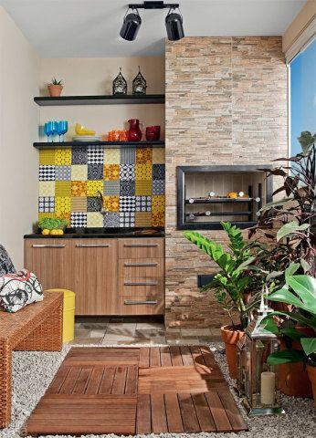 Esta varanda gourmet tem churrasqueira, deque e jardim vertical. Note que os pedriscos foram acomodados ao redor dos deques de madeira. Poupando na escolha de cada elemento, a paisagista Caterina Policonseguiu encaixar no orçamento um belo painel de azulejos coloridos.