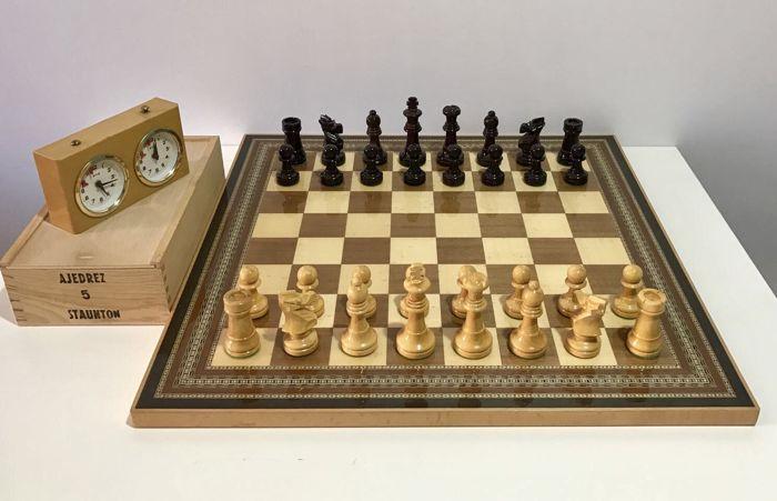 Club Schaken. Linares tentoonstelling stukken  Staunton 5 competitie schaakstukken. Het karakteristieke ontwerp van het schaak toernooien gehouden in Linares (Spanje) heeft in de jaren 1980-jaren 1990 met grote Schaken meesters. Dit is een speciale tentoonstellingsmodel met arabesque kenmerken van Andalusië. Stukken handgemaakt door geschoolde ambachtslieden van Granada. Een aantal goede grootte met een houten plank van inlegwerk van 50 x 50cm. Het bevat een klok van de Duitse concurrentie…