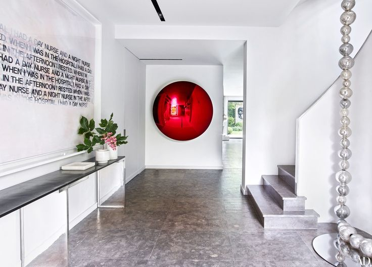 A deep-red Anish Kapoor sculpture greets visitors in the entrance hall of a Neuilly-sur-Seine, France, house designed by Charles Zana for a couple with a blue-chip contemporary-art collection. The text painting is by Richard Prince, and the console is by Eric Schmitt; a dramatic glass-bead sculpture by Jean-Michel Othoniel dangles from 30 feet above.