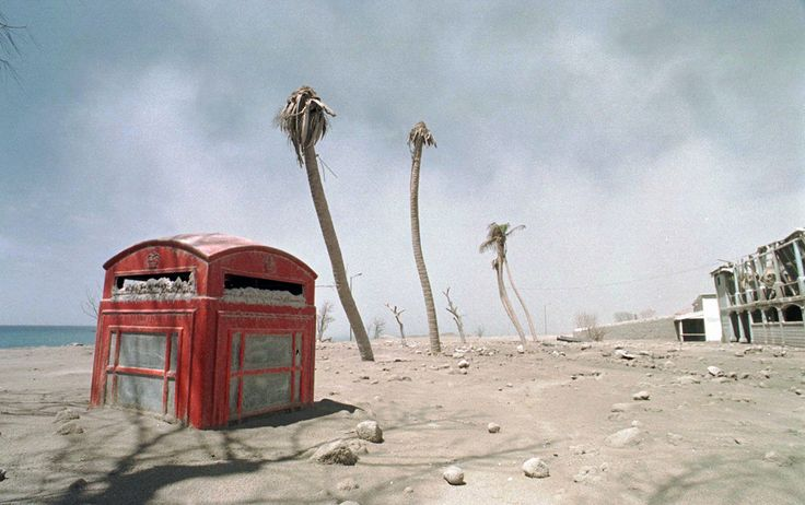 A red phone box lies half buried in volcanic ash in the exclusion zone in Montserrat, West Indies. .