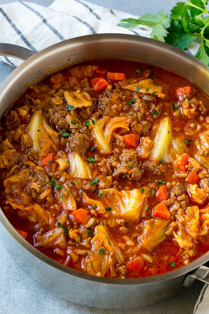 A pot full of cabbage roll soup garnished with parsley.