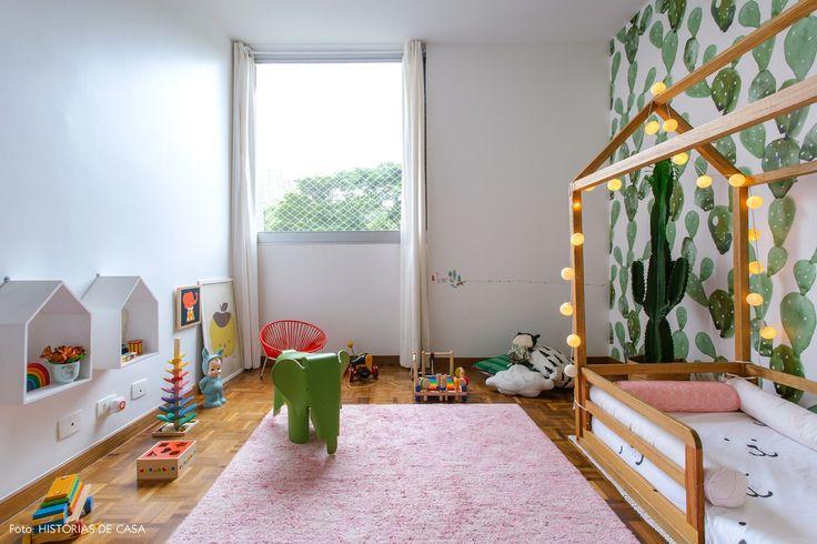 Quarto infantil tem papel de parede com estampa de cactos, tapete rosa e casinhas de madeira como prateleiras.