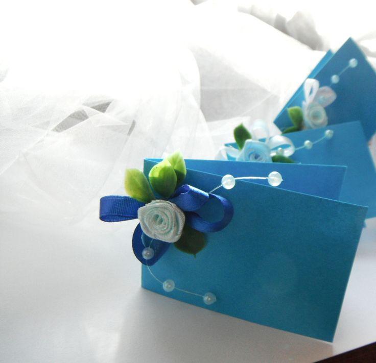 Svatební jmenovky - modré variace Svatební jmenovky zdobené modrou látkovou růžičkou a perličkami k dozdobení Vášeho svatebního stolu.Vyrobeny z pevného výkresového papíru.Lístky buxusu mohou být živé nebo umělé (zvolenou variantu připište k objednávce) Nabízíme v několika odstínech modré- zvolte si kombinaci dle Vašich představ. Výška 5cm délka 7cm ...