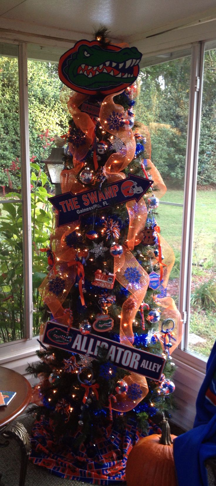 Gator Tree for this year.. 2014. Hand made yarn Pom Pom Ornaments. Glass balls filled w orange, blue and white mini Pom Poms. Gator head print out on cardboard. Cheap theme tree