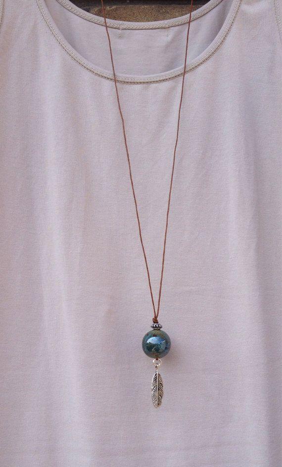 Ketting van waxkoord met onderaan een stenen kraal met blauw,groen en bruin tinten. Onder de steen hangt een zilverkleurige bedel van een veer. De